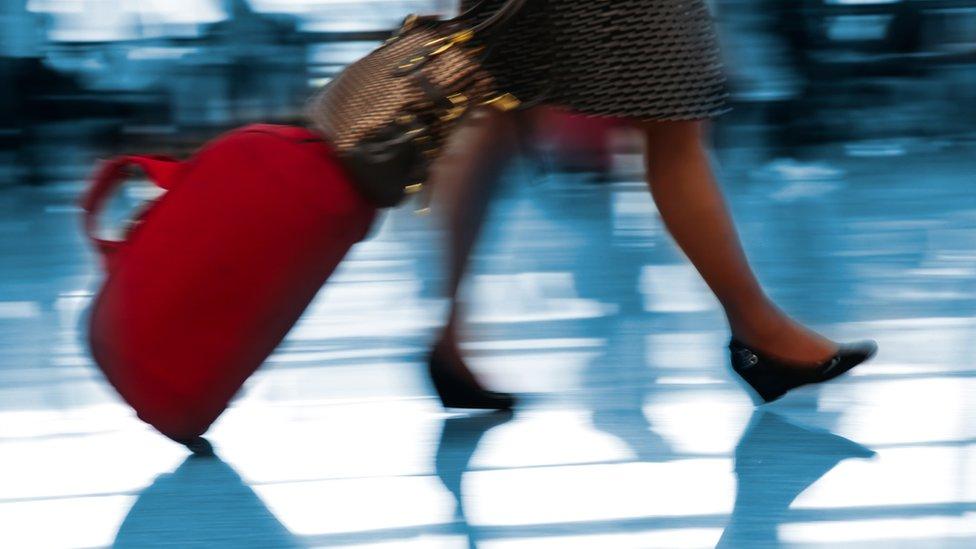 Una persona caminando por un aeropuerto con una maleta