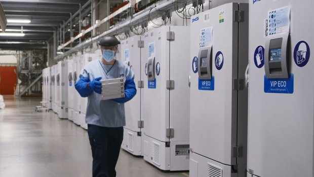 A worker passes a line of freezers holding coronavirus disease (COVID-19) vaccine candidate BNT162b2 at a Pfizer facility in Puurs, Belgium in an undated photograph.