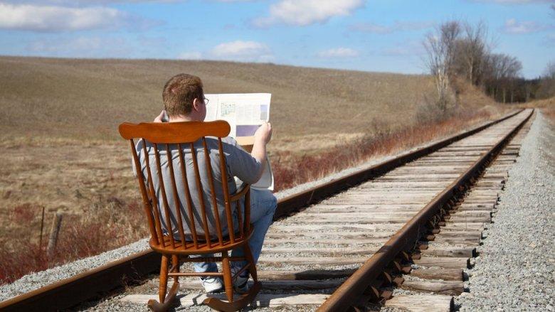 Hombre lee el periódico en las vías del tren