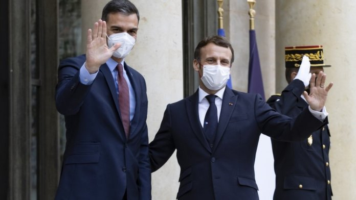 French President Emmanuel Macron (R) greets Spanish Prime Minister Pedro Sanchez (L)