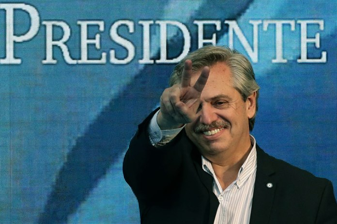 """Alberto Fernández con un cartel atrás que dice """"presidente"""""""