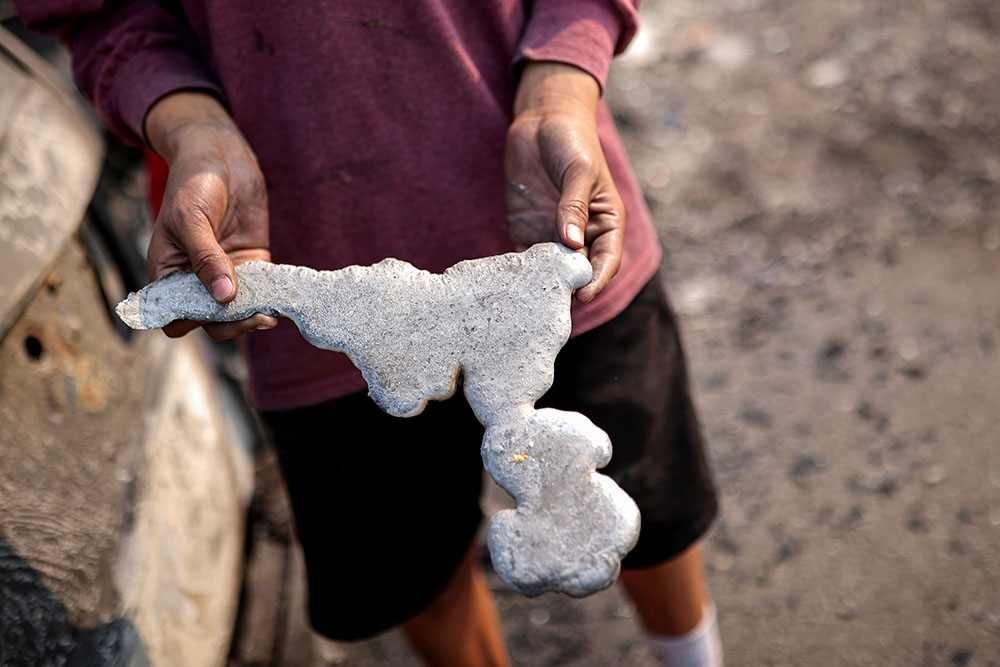 A man holds a piece of melted metal , Phoenix