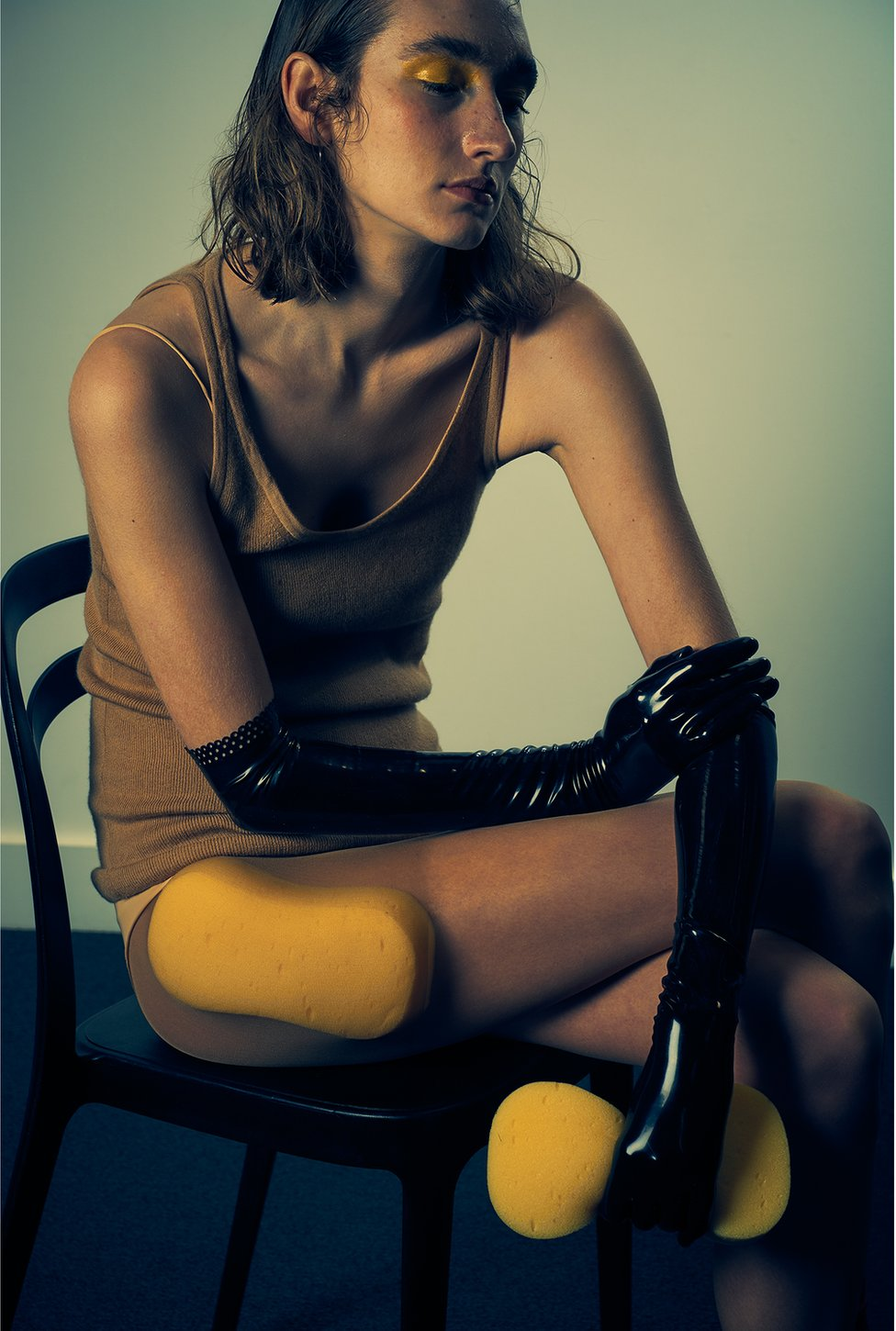 A model sits on a chair with a sponge clutched in her hand and one attached to her thigh