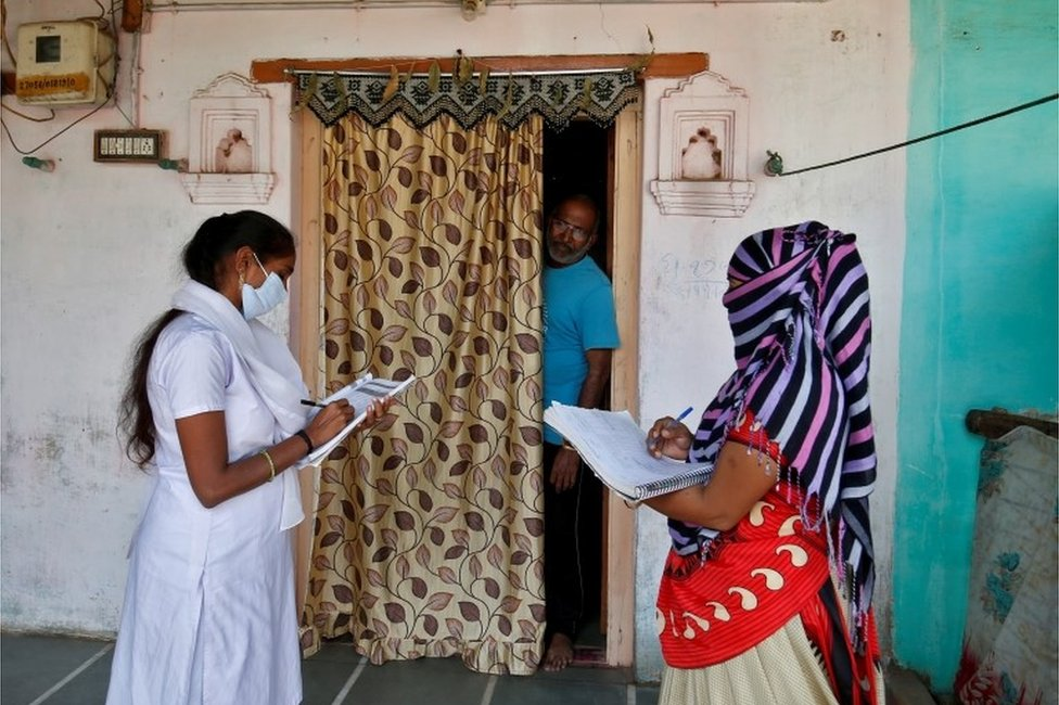 Health workers collect personal data from a man as they prepare a list during a door-to-door survey for the first shot of COVID-19 vaccine for people above 50 years of age and those with comorbidities, in a village on the outskirts of Ahmedabad, India, December 14, 2020.