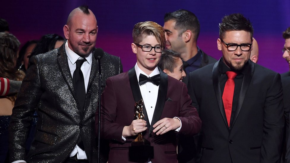 Bree Mills (centro) acepta el galardón a la Película del Año 2018, durante los Premios AVN, acompañada de su codirector Craven Moorehead (izq.) y el productor Billy Visual (der.)