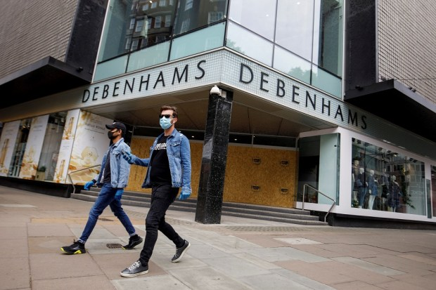 People walk past a boarded up Debenhams store