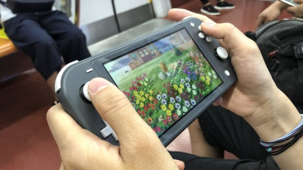 The hands of a person are seen playing Animal Crossing on the Nintendo Switch while on some form of train or underground transport