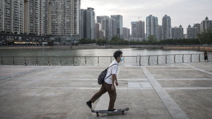 A man wears a mask plays skateboarding in Xibei lake park on May 11, 2020 in Wuhan, China.