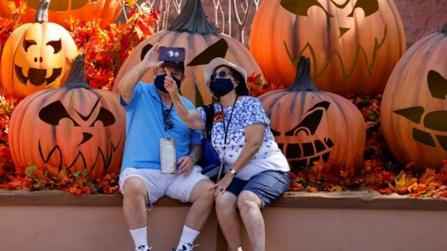 Couple in California wearing face masks taking a selfie in front of giant pumpkins