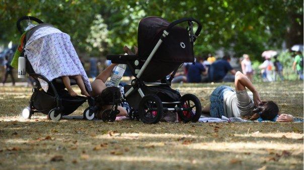 Una familia descansa a la sombra en un parque de Londres.