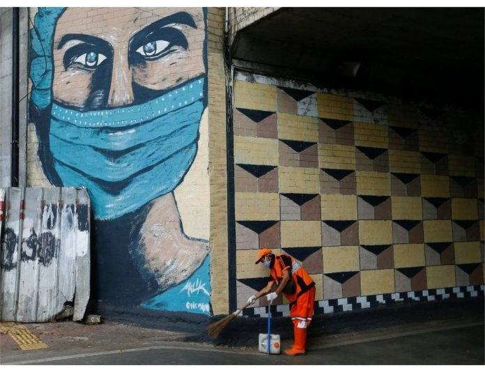 A worker wearing a protective face mask sweeps the street near a mural promoting awareness of the coronavirus disease (COVID-19) outbreak in Jakarta, Indonesia, October 2, 2020.