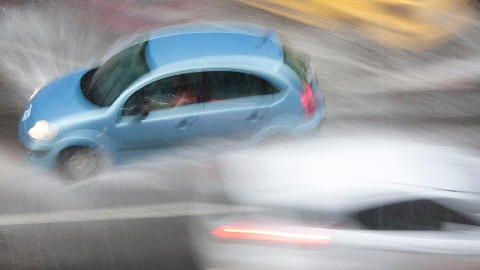 Un auto que parece pasar muy rápido al lado de otro, en una vía llena de agua