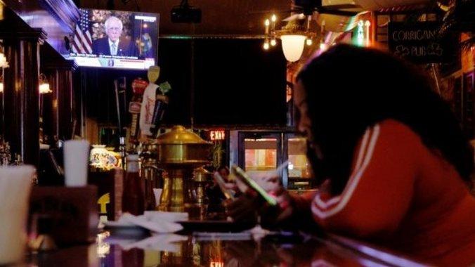 Una mujer en un bar mientras Bernie Sanders está en tv