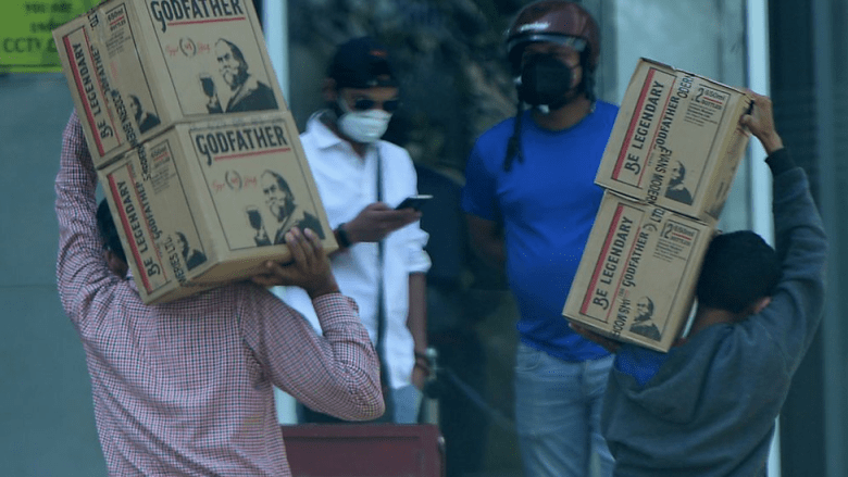 Two men carry boxes of liquor