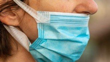 Maske takarken burnunu açıkta bırakmış bir kişi