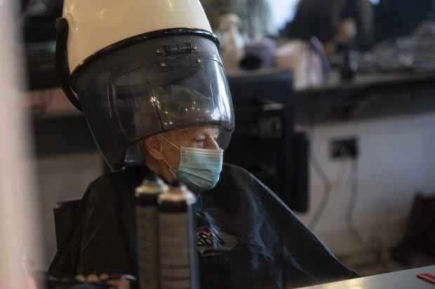An elderly woman wearing a mask in a hair salon