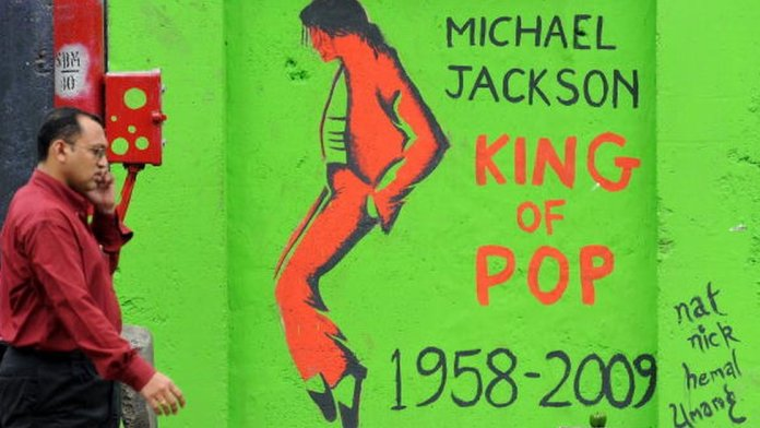 "An Indian pedestrian speaks into a cellular telephone as he walks past a grafitti image of the late ""King of Pop"" Michael Jackson on a wall in Mumbai on August 28, 2009,"