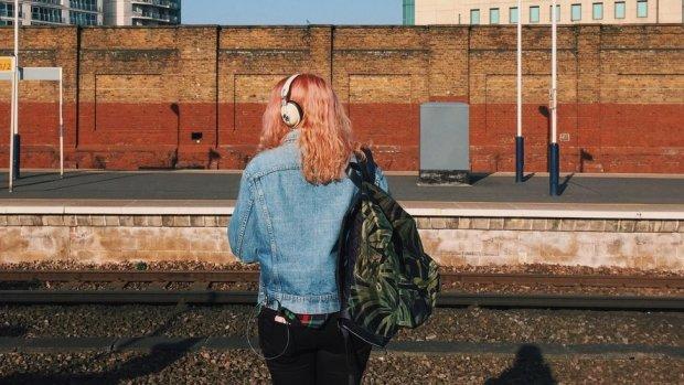 A woman waits at a train platform