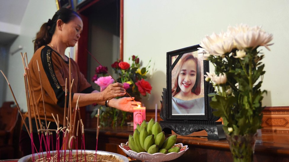 A relative lights an incense stick in front of a portrait of Bui Thi Nhung