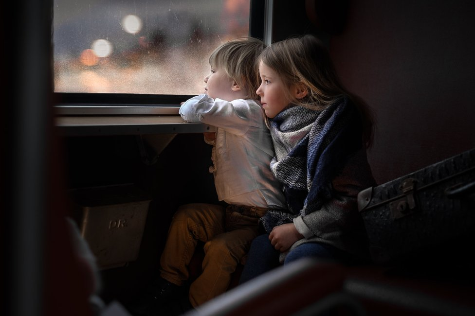 Two children looking out of a window