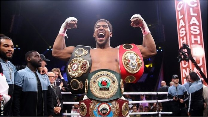 Anthony Joshua celebrates with im belts for ring after im beat Andy Ruiz Jr.