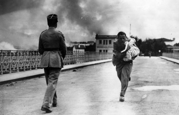 El periodista Raymond Walker, corre con un bebé en brazos sobre un puente entre Hendaya e Irún en plena guerra civil española.