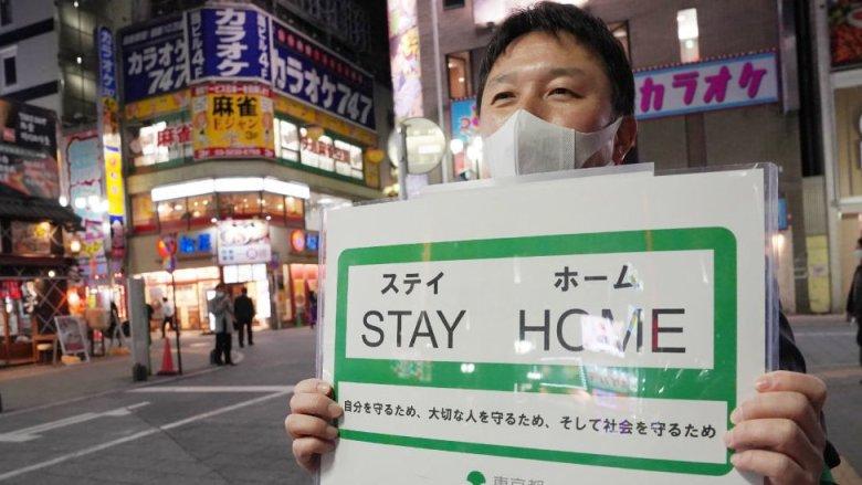 """Funcionario del gobierno municipal de Tokio con un carte de """"quédense en casa""""."""