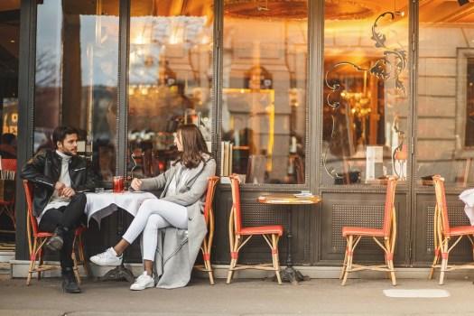 A couple sit outside a cafe in Paris