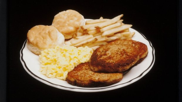 A meal featuring french fries, scones, scrambled egg and toast