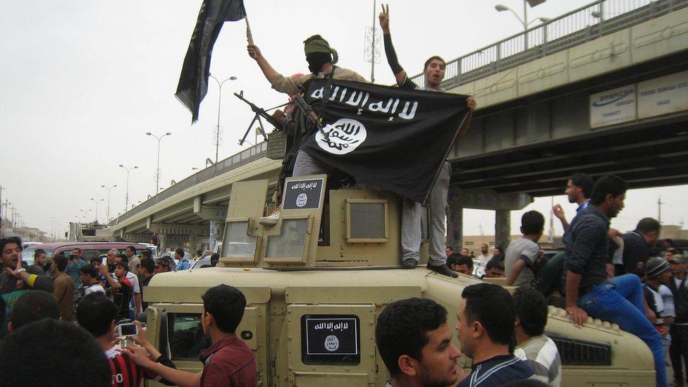 Militantes de Estado Islámico alzan su bandera mientras recorren Faluya en un vehículo militar.