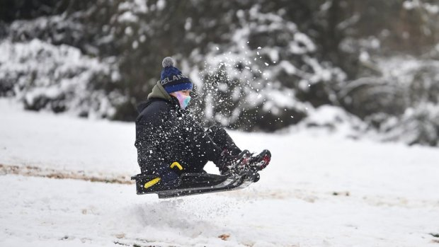 A woman wearing a mask rides a sledge down a hill on 29 December 2020 in Newcastle-Under-Lyme, England