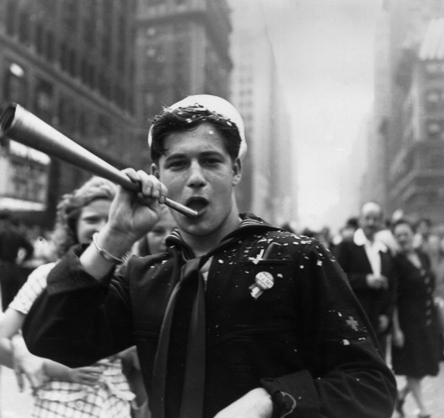 A sailor blows a trumpet in Times Square