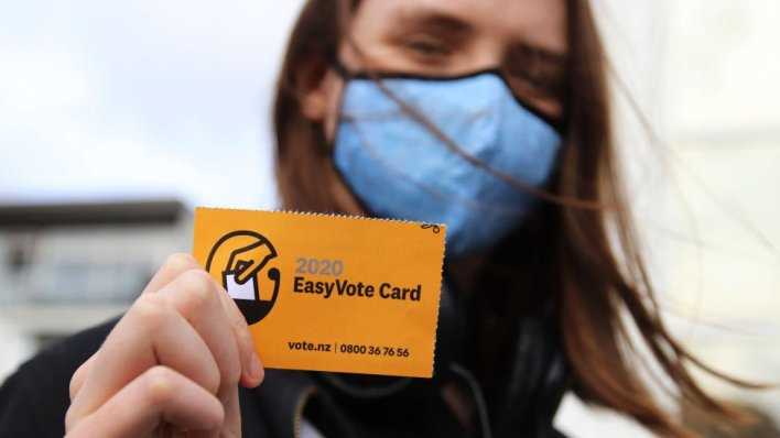 A young woman wearing a face mask holds up her Easy Vote card on the way to vote on the first day of advance voting