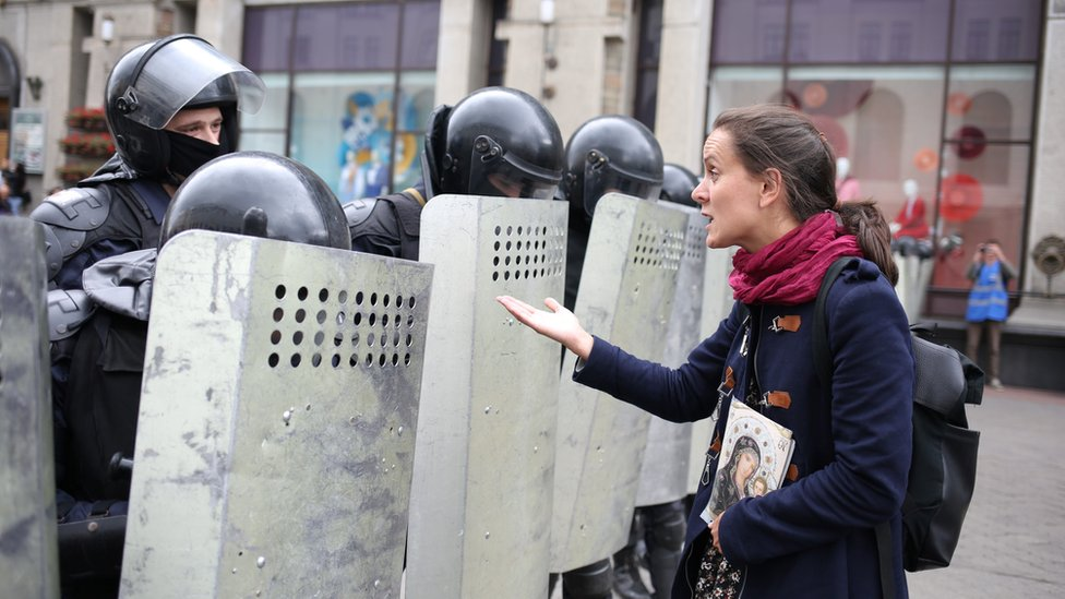 A woman addresses a Belarusian law enforcement officer during an opposition rally to protest against police brutality and to reject the presidential election results in Minsk, Belarus, 6 September