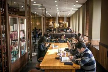"""Customers enjoy coffee and other drinks while working on their computers and iPads at a Starbucks in Seoul. """"At Starbucks, Koreans jumped on the bandwagon,"""" a professor says."""
