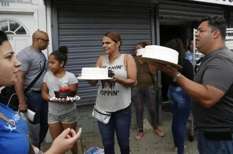 Lawrence, MA - 9/14/2018 - Carlos Alba (R) owner of Carlos Cake and Flowers gave away cakes outside his shop in Lawrence. (Jessica Rinaldi / Globe Staff) Topic: 15Lawrence Reporter: