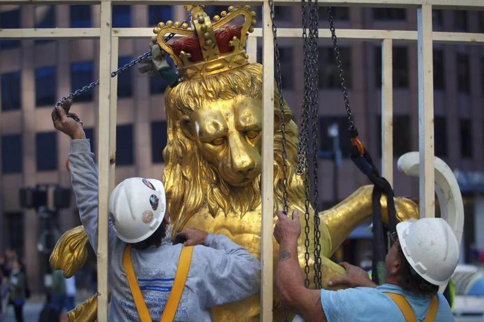 An iconic statue of a lion atop the Old State House on Washington Street in Boston was hoisted down from its rooftop perch for restoration.