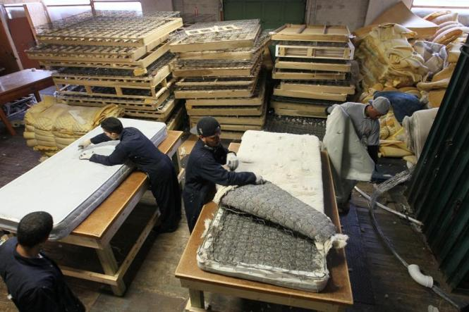A Worker In Lawrence Began The Process Of Taking Apart Mattress For Recycling