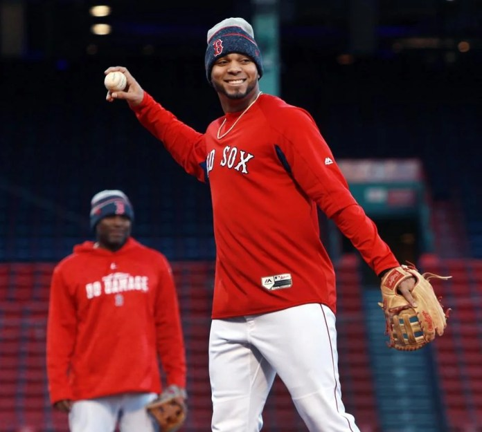 It's cool in Fenway, and Xander Bogaerts had his cap on his head as he played catching before batting.