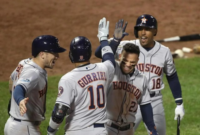 Boston, MA 10/13/18: Astros Jose Altuve (second from right) and Tony McCann (back right) congratulates teammate Yuli Gurriel on his three run home run in the ninth inning. Boston Red Sox hosted the Houston Astros in Game One of ALCS at Fenway Park Saturday, Oct. 13, 2018. (Stan Grossfeld/Globe Staff)