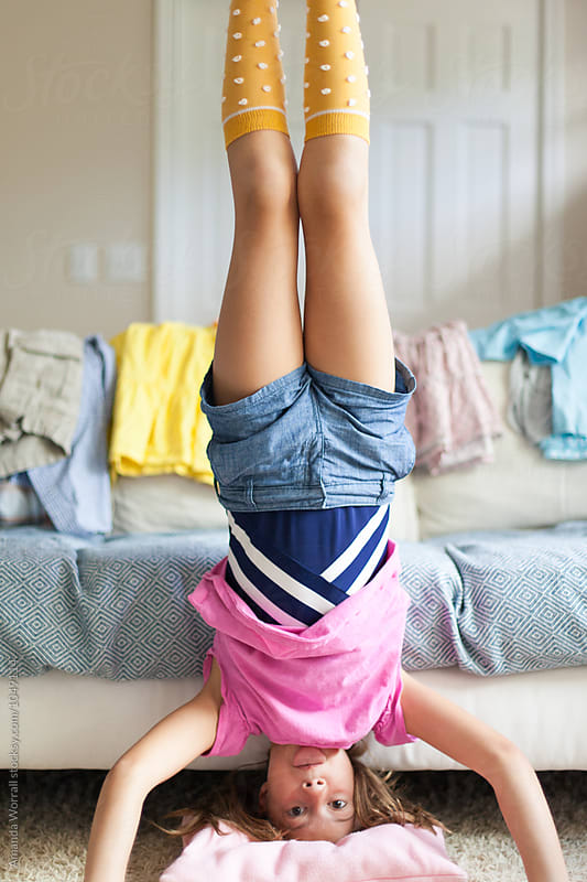 Tween Girl Doing A Headstand At Home In A Messy Living