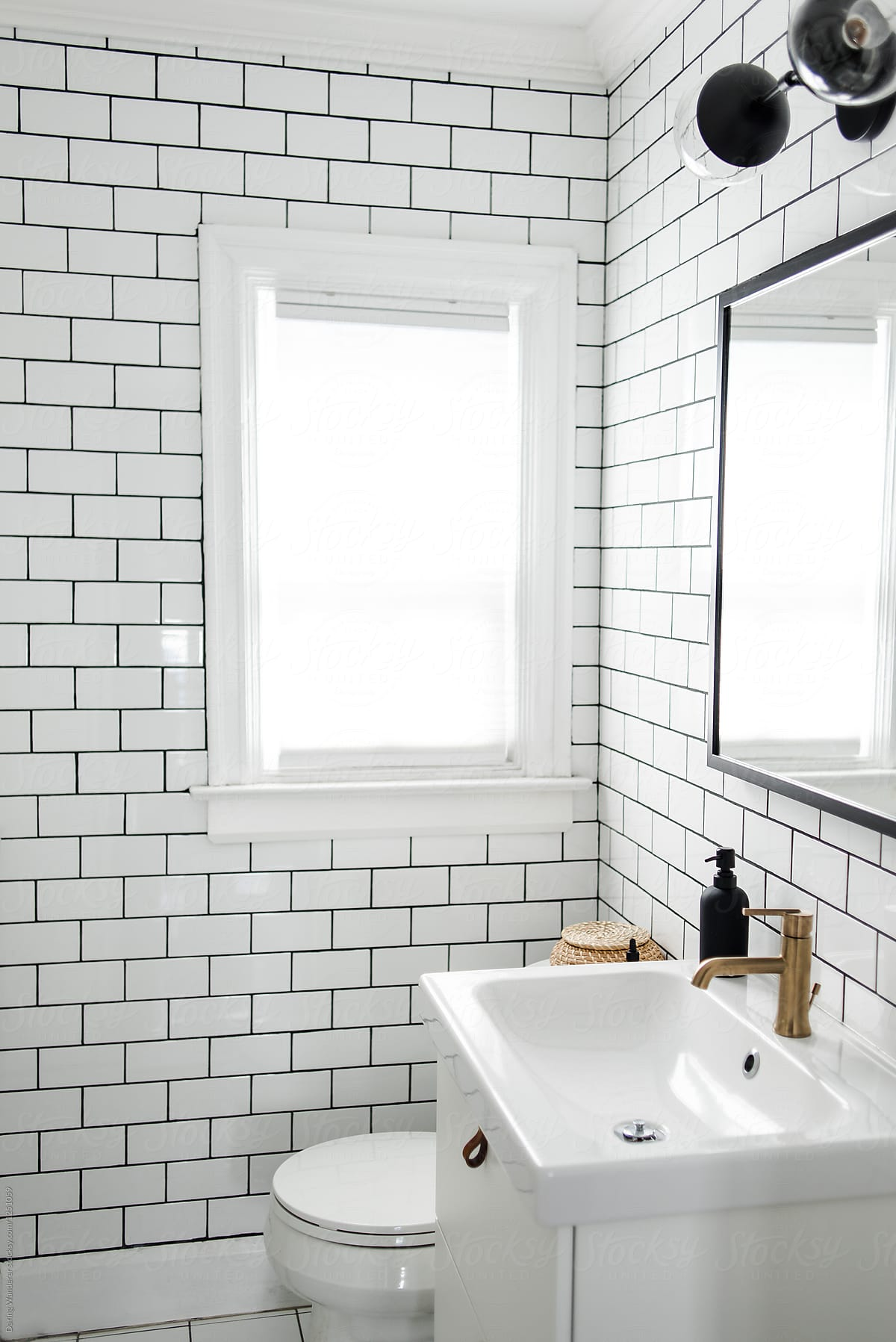 minimalist small bathroom renovation with white subway tile and ikea cabinet by jess craven for stocksy united