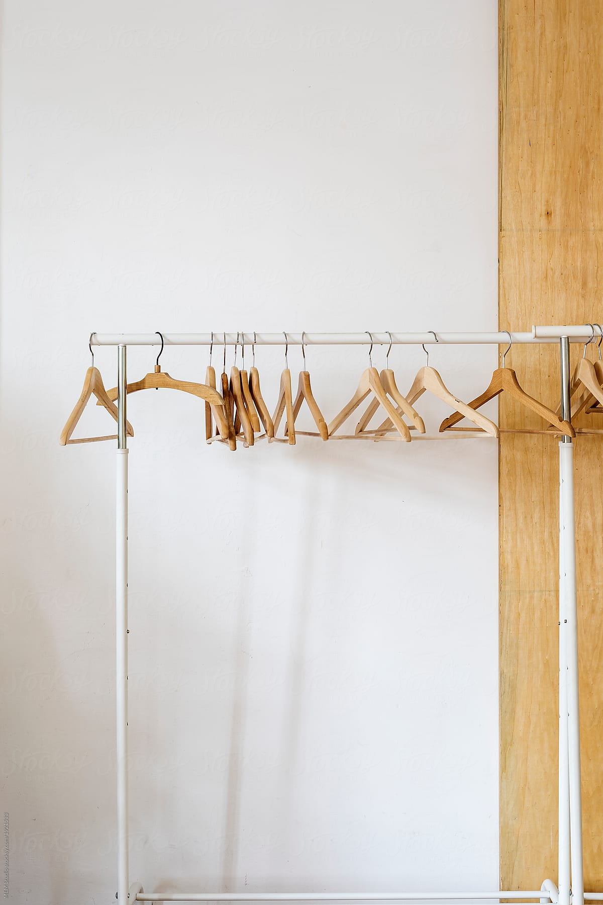 empty wooden clothes hangers on a clothes rack by mem studio for stocksy united