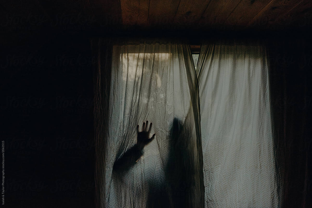 a shadowed silhouette of a person hiding behind a curtain reaching hand out against surface by isaiah taylor photography for stocksy united