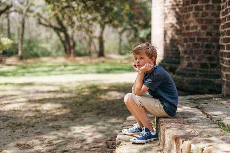 bored boy sitting alone at a park by Kelly Knox - Stocksy United