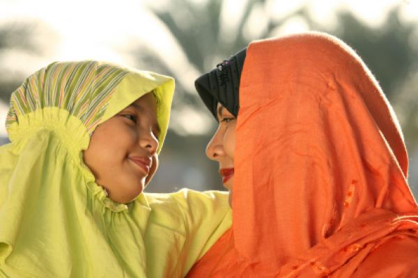 Muslim child and mother expressing joy.