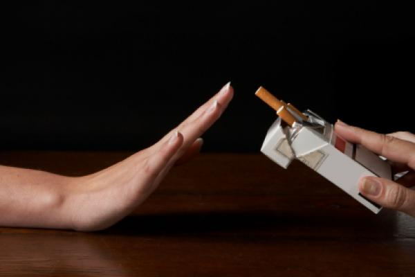 Hand saying no thanks to a packages of cigarettes offered