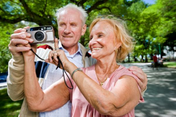 An senior couple with a camera, touring on vacation.