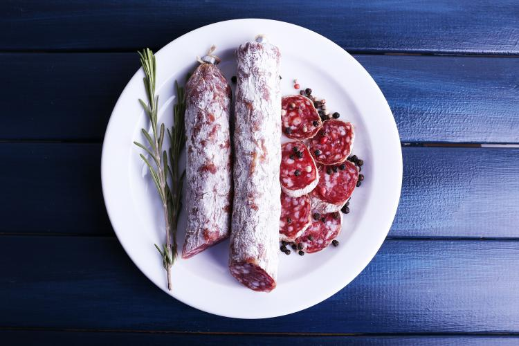 French salami on plate on dark blue wooden background.