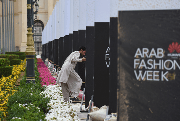 A labourer prepares signs ahead of the opening ceremony of the Arab Fashion Week, on April 10, 2018, at Ritz Carlton hotel in the Saudi capital Riyadh. / AFP PHOTO / FAYEZ NURELDINE